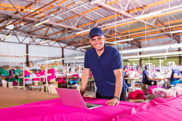 man standing at event booth with laptop