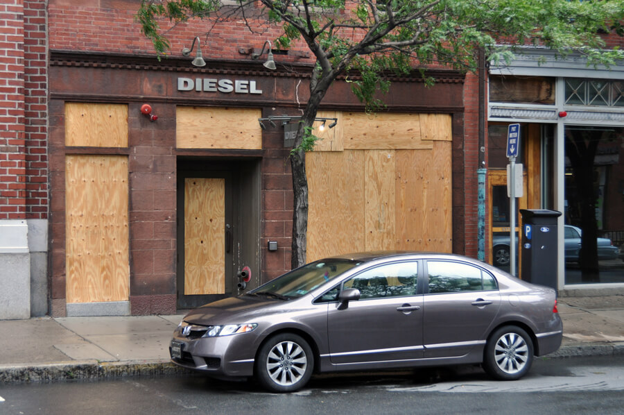 a car parked out front of a boarded up business