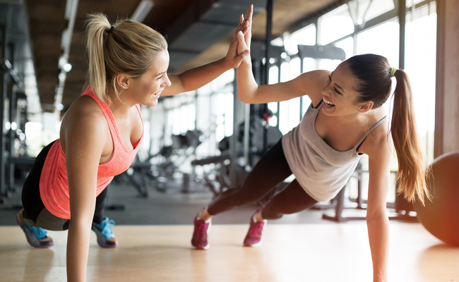 two women working out and high fiving