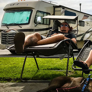 couple lounging in front of their RV