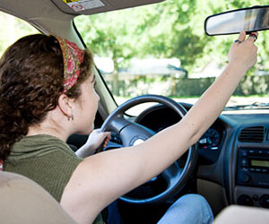 teenage girl adjusting rear view mirror in car